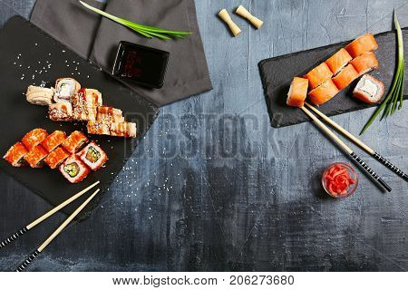 Japanese sushi rolls set with salmon shrimp sesame and cream cheese on stone slate with chopsticks and fresh greens with soy sauce and ginger on dark copyspace background