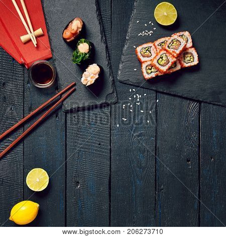 Japanese sushi rolls and gunkan sushi set with salmon shrimp sesame and cream cheese on stone slate with chopsticks and lemon with soy sauce and ginger on dark wooden copyspace background