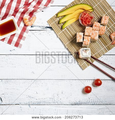 Japanese sushi rolls set with salmon shrimp bonito and cream cheese on bamboo napkin with chopsticks and fresh food ingredients with soy sauce and ginger on white wood copyspace background