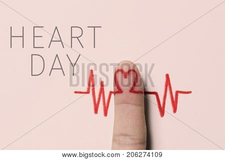 a red heart symbol in the forefinger of a man as in an electrocardiogram painted on a pink background and the text heart day