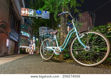 TOKYO, JAPAN - NOVEMBER 13, 2016: Bicycle on the street of Tokyo at night, Japan. Tokyo Metropolis is both the capital and most populous city of Japan.