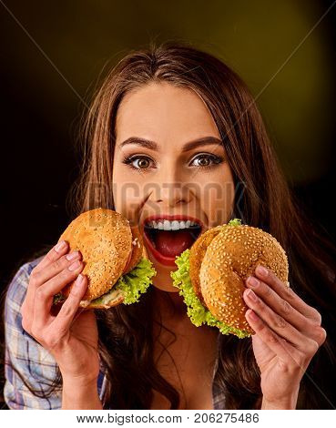 Upset girl holding big two small hamburgers and pizza. Fastfood concept on green background. Disruption from diet.