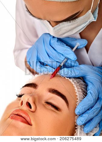Filler injection for female forehead face. Plastic aesthetic facial surgery by doctor in beauty clinic. Facing skin with Botox. Doctor in medical gloves with syringe. Wrinkle removal.