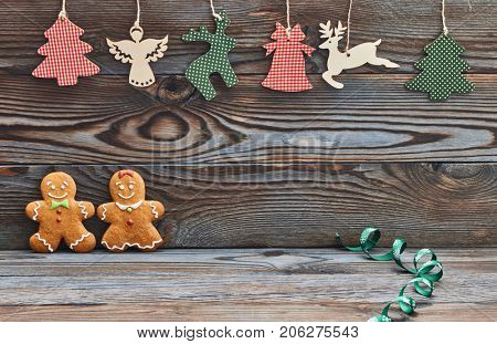 Christmas homemade gingerbread cookies on wooden background. Gingerbread couple - man and woman.