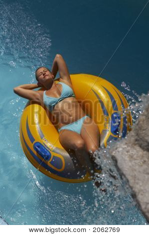 A Young Woman Is Lying On A Floating Tire