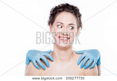 Conceptual portrait of a young woman pulled by aesthetic industry. Young woman being grabbed by hands in gloves.