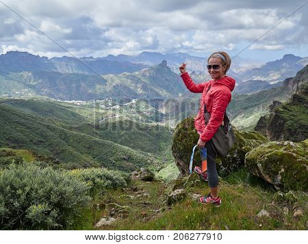 Young woman tourist standing on cliff's edge admiring landscape, Gran Canaria, Spain