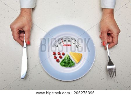 hands with kitchen flatware and healthy food in plate