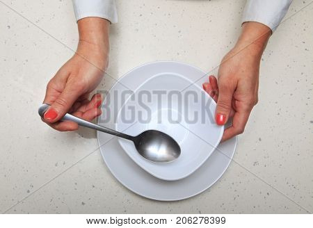 hands of woman who holds spoon and plate