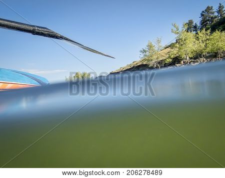 Stand up paddling on a mountain lake, partially underwater abstract shot