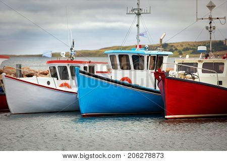 Blue, white and red fishing boats at the pier in Havre Aubert in Quebec, Canada