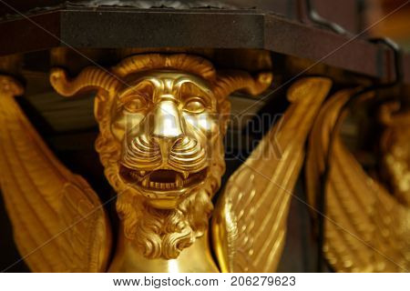 Antique bronze lion mask fixed to a wall.