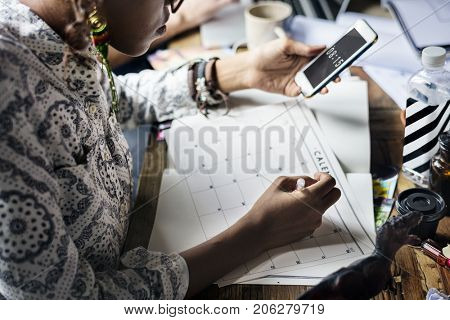 Woman Planning Writing Note on Calendar