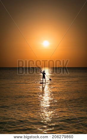 Silhouette of man standing up at paddle Board on sunset, White beach, Boracay. Philiphines.