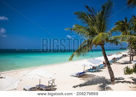 Tropical vacation on white sand beach with sun, blue sky and palm trees. White beach at Boracay island, Philiphines.