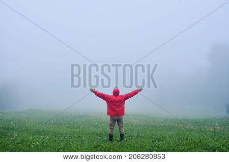 Rear view of man with hands up admiring foggy morning