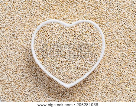 Quinoa in heart-shaped bowl on quinoa background. Gluten free ancient grain for healthy diet. I love quinoa concept. Copy space.