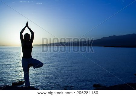 Beauty girl on beach in yoga pose, relax silhouette.