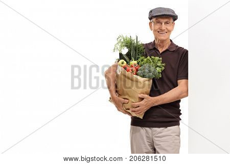 Elderly man holding a paper bag filled with groceries and leaning against a wall isolated on white background