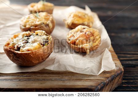 Baked stuffed potatoes on wooden board, close up