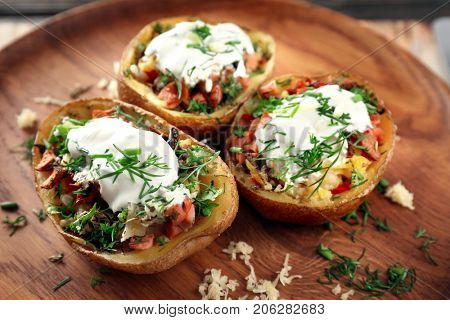 Baked stuffed potatoes on wooden plate, close up