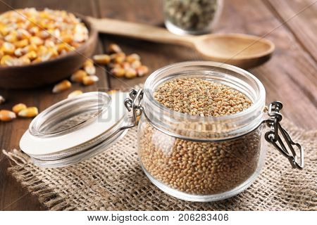 Jar with millet grains on table