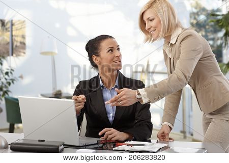 Business teamwork at the office - businesswomen working at desk.