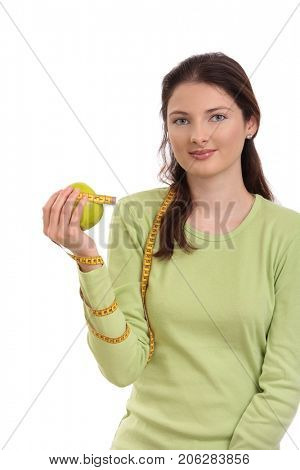 Healthy teenage girl holding apple, measuring tape circled around arm, looking at camera, smiling. Isolated on white.