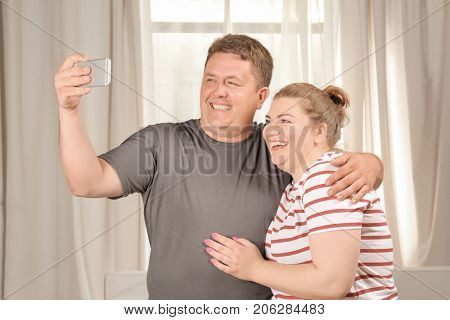 Overweight couple taking selfie at home