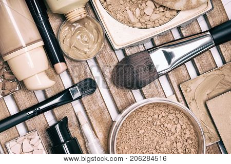 Set of foundation makeup products on wooden stand. Concealer stick, primer, liquid and cream foundation, different types of powder with make up brushes
