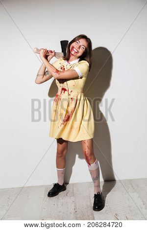 Full length image of smiling zombie woman in dress attacking with an axe and looking at the camera over white background