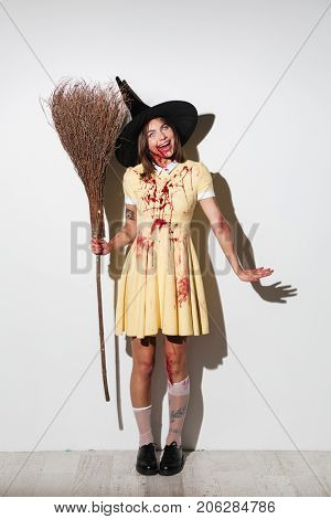 Full length image of crazy happy woman in halloween costume holding broom and looking at the camera over white background