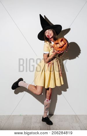 Full length image of Pleased crazy woman in halloween costume moving with curved pumpkin and looking at the camera over white background