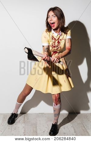 Full length image of crazy zombie woman in dress attacking with an axe and looking at the camera over white background