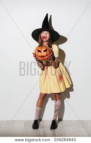 Full length image of Laughing woman in halloween costume holding curved pumpkin and looking at the camera