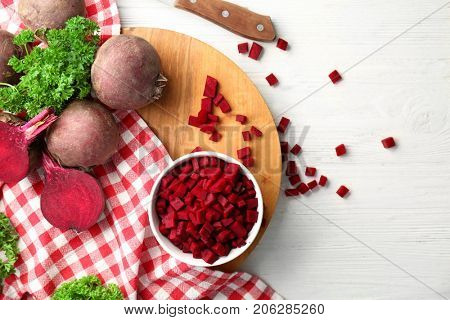 Composition with sliced beetroot on white wooden background