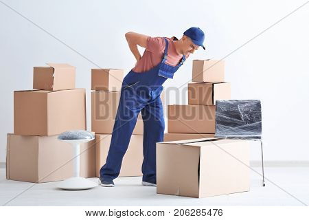 Man suffering from back ache while moving boxes, indoors
