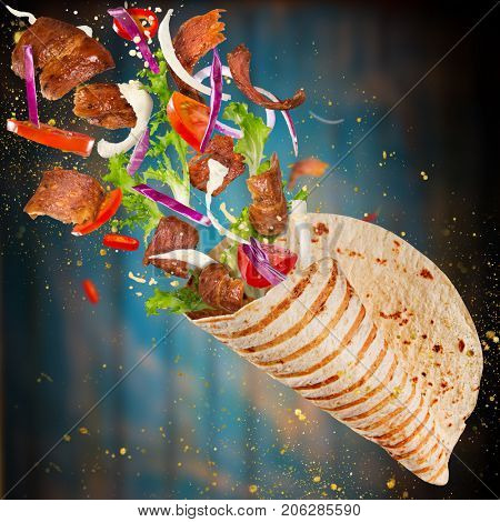 Close-up of kebab sandwich with flying ingredients. Freeze motion.