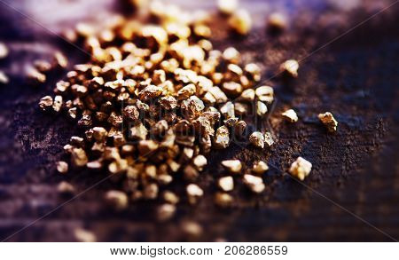 Small pile of gold nuggets on a rough wooden work table. Grungy tone and extremely shallow depth of field for impression-like tone.