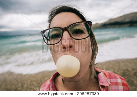 Young woman with a stylish eyewear inflates a chewing gum.