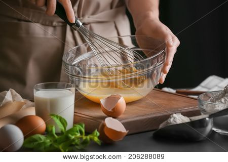 Female chef whisking eggs in glass bowl on kitchen table