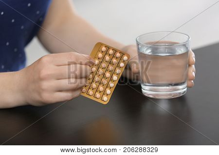 Woman with birth control pills and glass of water at table