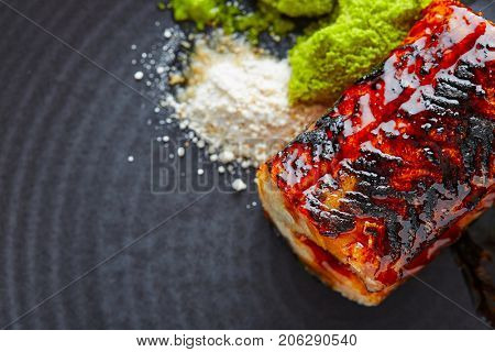 Grilled smoked eel with green apple and citrus on black plate