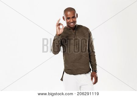 Smiling african man showing ok sign and looking at the camera over white background