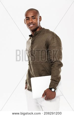 Vertical side view image of Smiling african man holding laptop computer and looking at the camera over white background