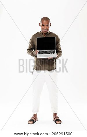 Full length image of happy african man showing blank laptop computer screen and looking at the camera over white background