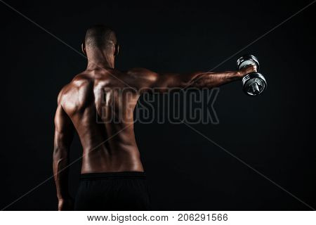 Back view photo of half-naked muscular sports man, with dumbbell in right hand, isolated on black background