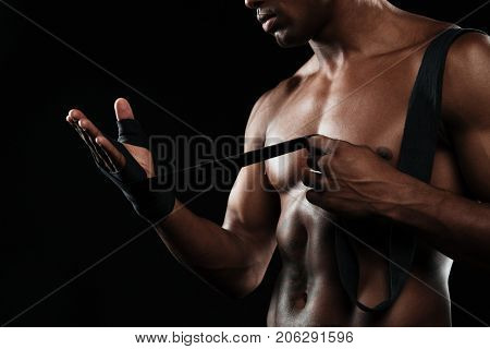 Cropped photo of the hands young afroamerican boxer who winds boxing bandages before a match fight or training, over black background