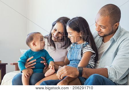 Multiethnic family playing with happy baby son at home. Parent and children relaxing together on the sofa at home in the living room. Little girl sitting on leg of dad looking her new cute brother.