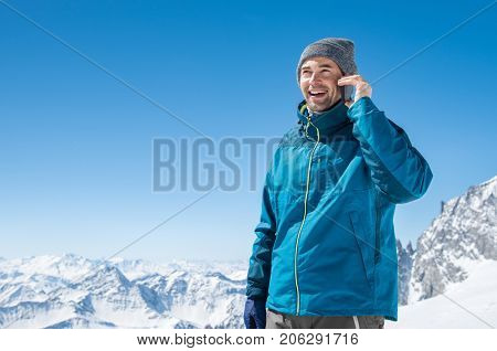 Portrait of a young man talking on mobile phone on snowy mountain. Happy guy using cellphone in winter holiday with copy space. Smiling man has a joyful conversation at phone.